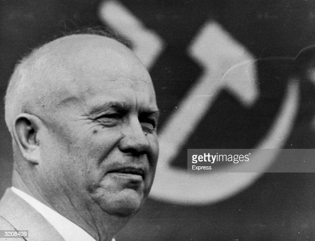 Headshot of former Soviet Premier Nikita Khrushchev with the hammer and sickle symbol behind him