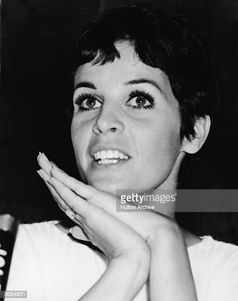 Headshot of French singer and actor Claudine Longet clasping her hands at a microphone during a visit to Japan circa 1968