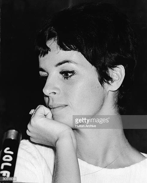 Headshot of French singer and actor Claudine Longet sitting at a microphone with her chin propped in her hand during a visit to Japan circa 1968