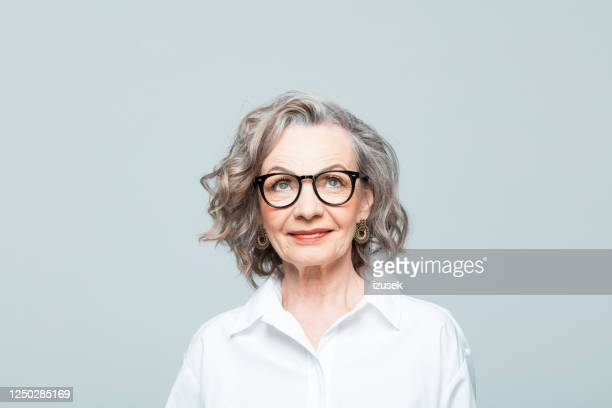headshot of friendly senior woman in white shirt - decisions stock pictures, royalty-free photos & images