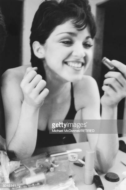 Headshot of future American pop singer Madonna laughing while leaning towards a mirror to apply lipstick New York City Her hair is short and dark and...