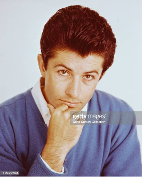 Headshot of George Chakiris, US dancer, singer and actor, wearing a white shirt beneath a blue jumper, with his chin resting on his hand, circa 1965.