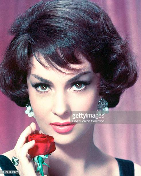 Headshot of Gina Lollobrigida Italian actress wearing pearl earrings and holding a red rose to her chin in a studio portrait circa 1955