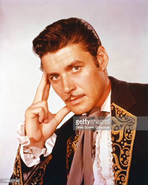 Headshot of Guy Williams US actor wearing a mariachi costume with his head resting on his right hand in a studio portrait against a white background...