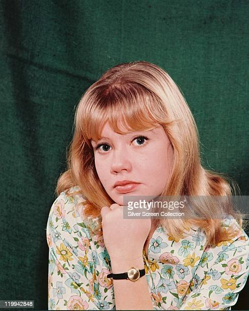 Headshot of Hayley Mills British actress wearing floral patterned blouse with her chin resting on her hand in a studio portrait against a green...