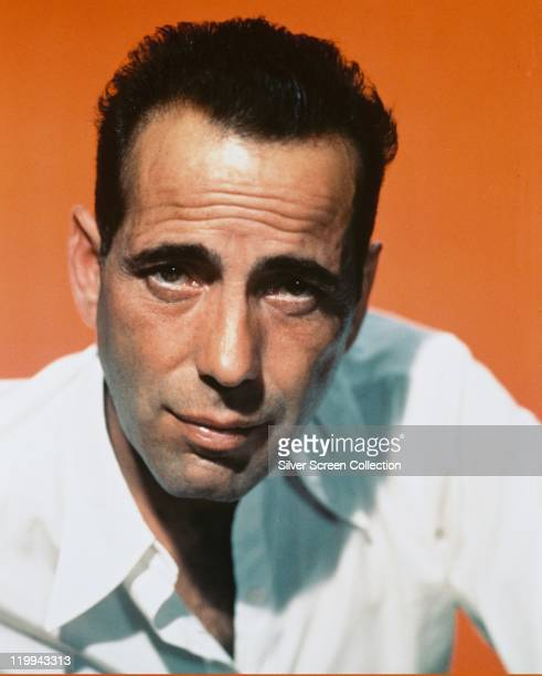 Headshot of Humphrey Bogart , US actor, wearing a white open-necked shirt in a studio portrait, against an orange background, circa 1940.