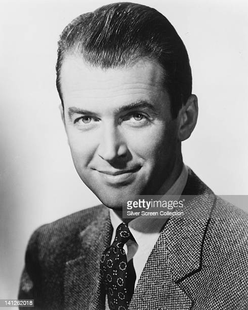 Headshot of James Stewart US actor wearing a tweed jacket a white shirt and tie in a studio portrait against a white background circa 1945