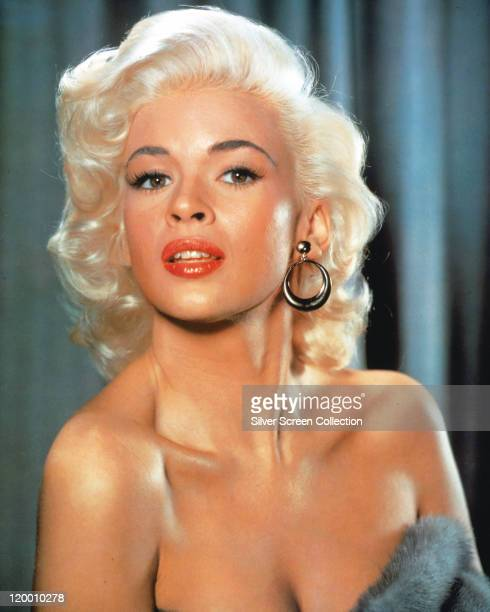 Headshot of Jayne Mansfield US actress wearing circular earrings in a studio portrait against a bluebackground circa 1955