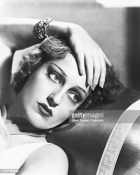 Headshot of Jeanette MacDonald US singer and actress posing with her left hand on her head which rests against the backrest of a sofa in a studio...