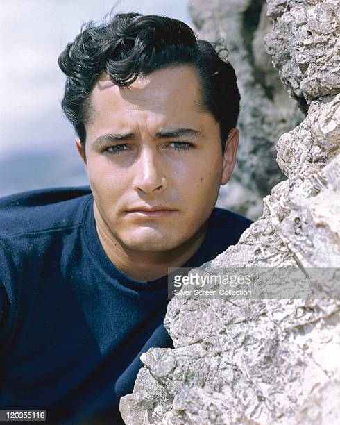 Headshot of John Derek , US actor and film director, poses beside a rockface, circa 1955.