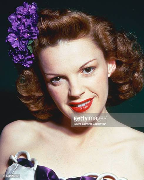 Headshot of Judy Garland US actress and singer wearing a purple flower in her hair in a studio portrait against a dark background circa 1945