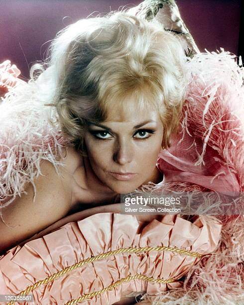 Headshot of Kim Novak, US actress, surrounded by pink ostrich feathers in a studio portrait, circa 1960.