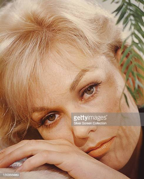 Headshot of Kim Novak US actress with a twig bearing leaves hagning down to the right of the image circa 1965