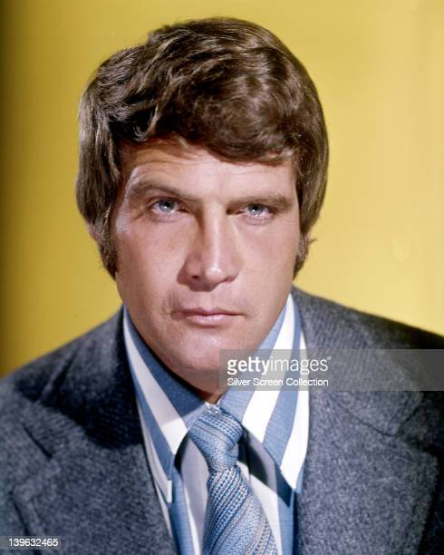 Headshot of Lee Majors, US actor,wearing a grey jacket, a blue and white striped shirt and a blue tie in a studio portrait, against a yellow...