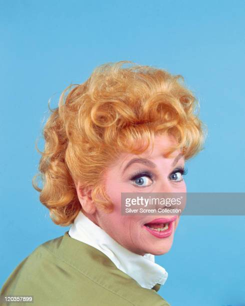 Headshot of Lucille Ball US actress and comedian looking over her right shoulder in a studio portrait against a blue background circa 1955