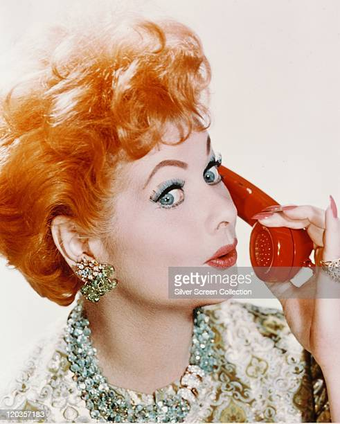 Headshot of Lucille Ball US comedian and actress holding a red telephone receiver in a studio portrait against a white background circa 1960