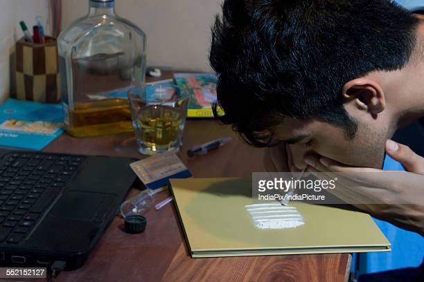 Headshot of man snorting cocaine at home