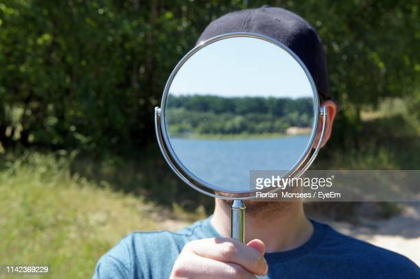 headshot of man standing with mirror covering face - hand mirror stock pictures, royalty-free photos & images