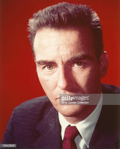 Headshot of Montgomery Clift US actor wearing a dark blue jacket a white shirt and a red tie in a studio portrait against a red background circa 1955