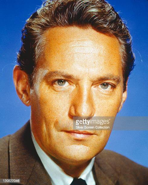 Headshot of Peter Finch Australian actor in a studio portrait against a blue background circa 1960