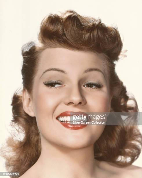 Headshot of Rita Hayworth US actress and dancer smiling in a studio portrait against a white background circa 1950