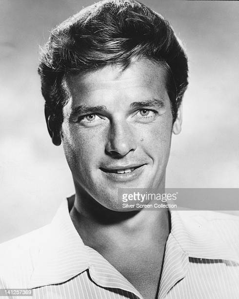 Headshot of Roger Moore British actor smiling and wearing striped shirt in a studio portrait against a light background circa 1965
