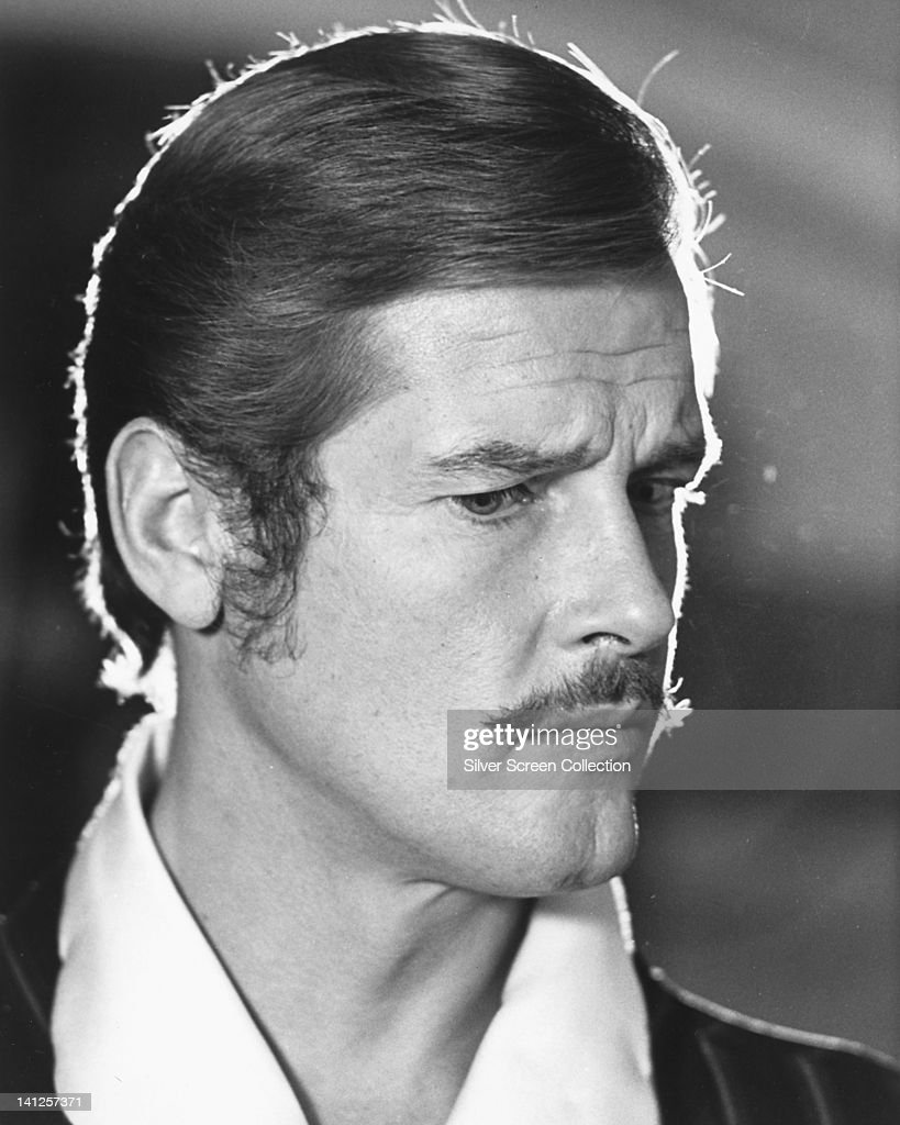 Headshot of Roger Moore, British actor, with a moustache, with his head turned to the right of the image, circa 1970.