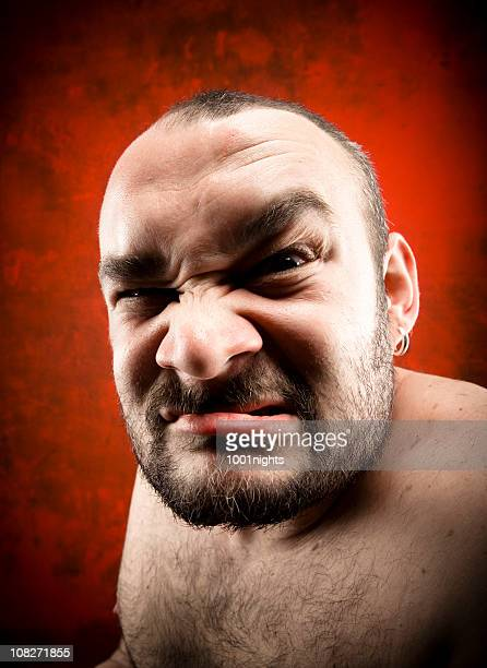 headshot of shirtless and bearded man scowling - ugly bald man stock photos and pictures