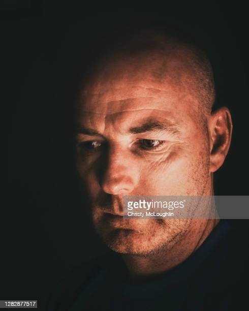 headshot of skinhead stubbled mature man with contemplative facial expression - skinhead stock pictures, royalty-free photos & images