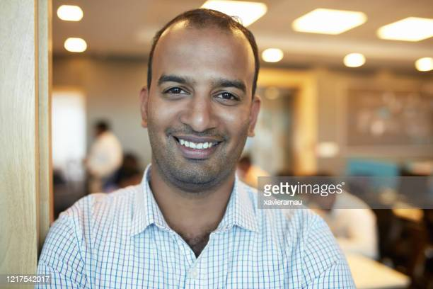 headshot of smiling mid adult indian male office worker - printed sleeve stock pictures, royalty-free photos & images