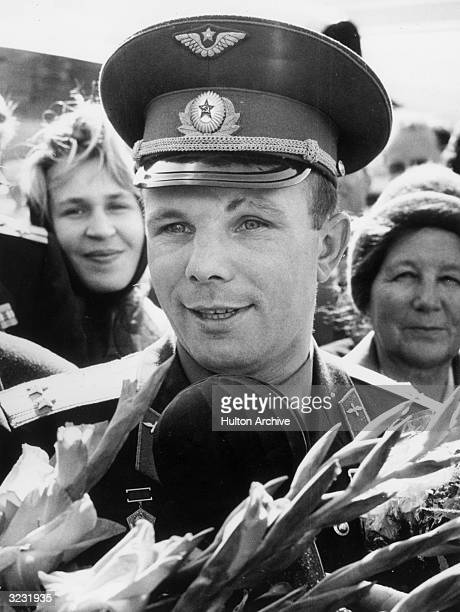 Headshot of Soviet cosmonaut Yuri Gagarin speaking into a microphone while surrounded by a crowd of wellwishers outdoors