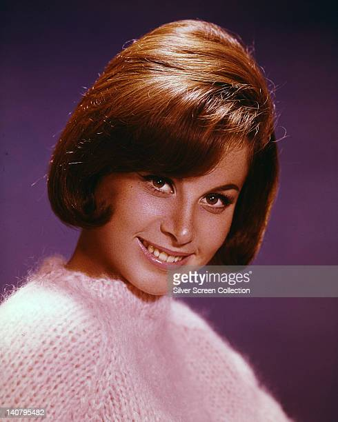 Headshot of Stefanie Powers US actress wearing a pink jumper in a studio portrait against a purple background circa 1965