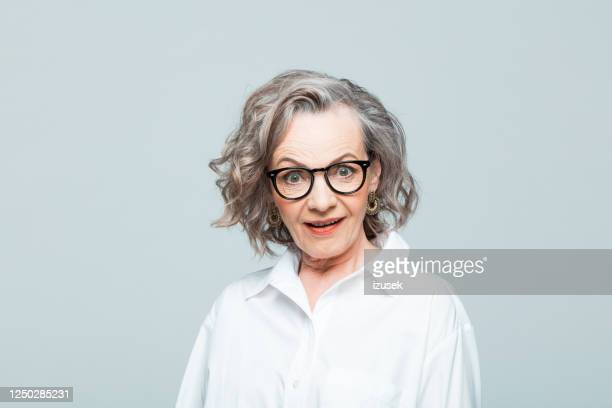 headshot of surprised senior woman in white shirt - surprise stock pictures, royalty-free photos & images
