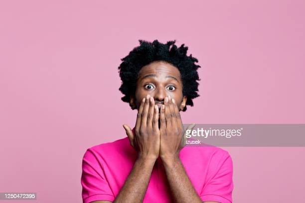 headshot of surprised young man wearing pink polo shirt - surprise stock pictures, royalty-free photos & images