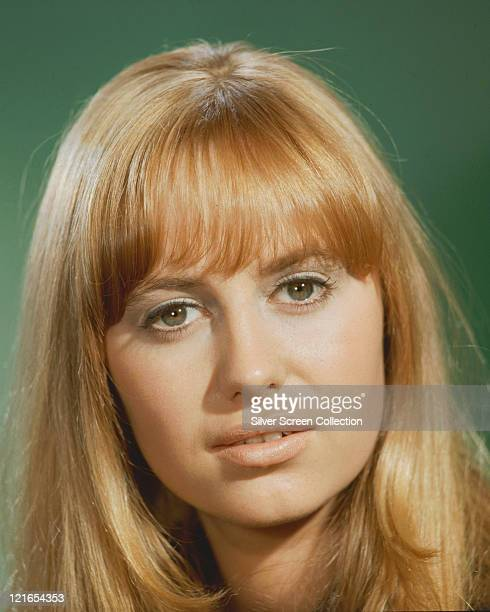Headshot of Susan George British actress in a studio portrait against a green background circa 1975