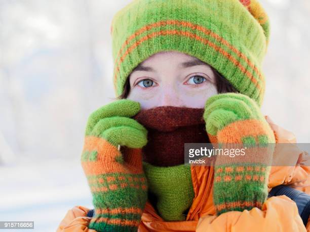 headshot of woman adjusting green winter hat and scarf - mitten stock pictures, royalty-free photos & images