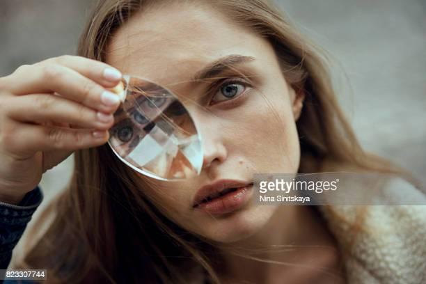Headshot of woman holding glass crystal near her eye