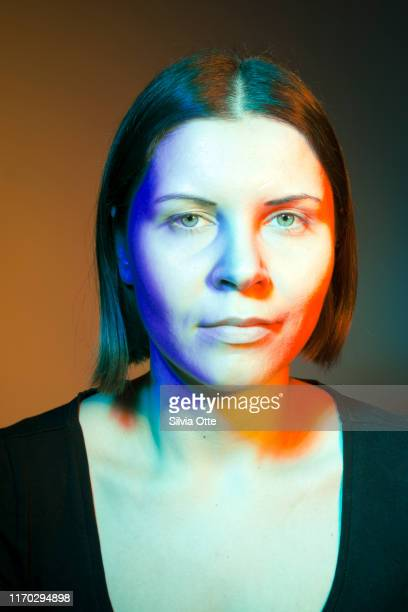 headshot of young adult woman in studio, lit with multiple colour lights - junge frau rätsel stock-fotos und bilder