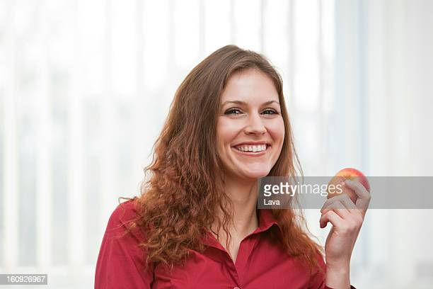 headshot of young businesswoman holding apple