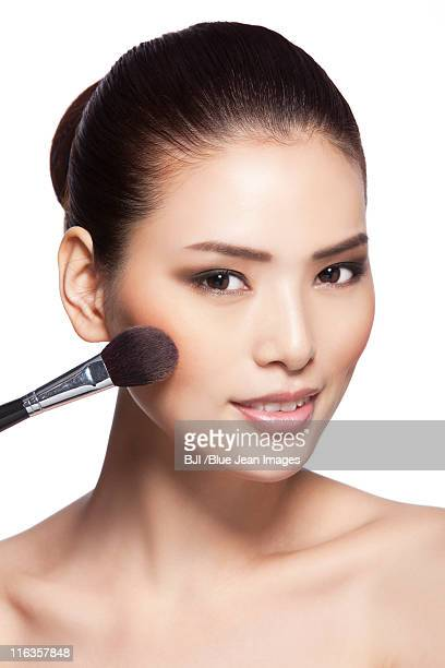 Headshot of young woman applying makeup
