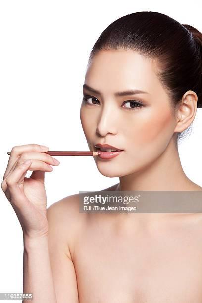 Headshot of young woman applying makeup