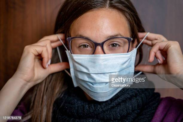 headshot of young woman in eyeglasses applying surgical mask on her face looking at camera - stock photo - single use stock pictures, royalty-free photos & images
