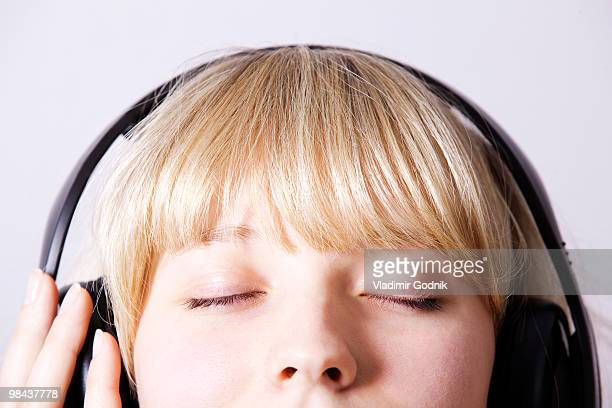 headshot of young woman listening to music with headphones