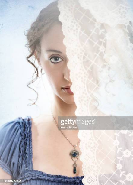 headshot of young woman with red hair in curled updo with regency-style clothing looking at camera, half hidden behind lace curtain, studio shot - authority stock pictures, royalty-free photos & images