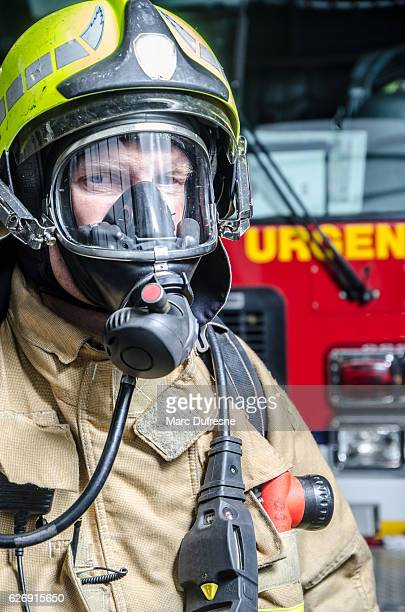 Headshot on fireman wearing full protection equipment and truck