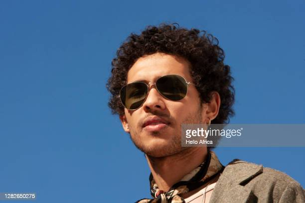 headshot portrait of a handsome young man with clear blue sky as background - sunglasses stock pictures, royalty-free photos & images