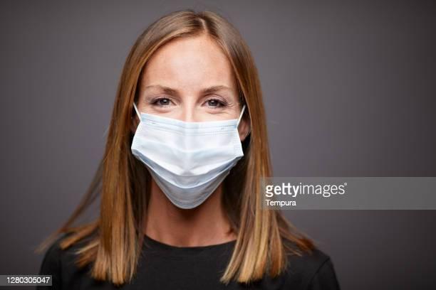 headshot portrait of a young woman wearing a protective mask - só adultos imagens e fotografias de stock