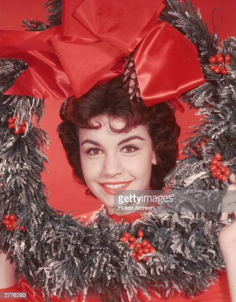 Headshot portrait of American actor and singer Annette Funicello posing with her head encircled by a decorative Christmas wreath circa 1955 There is...