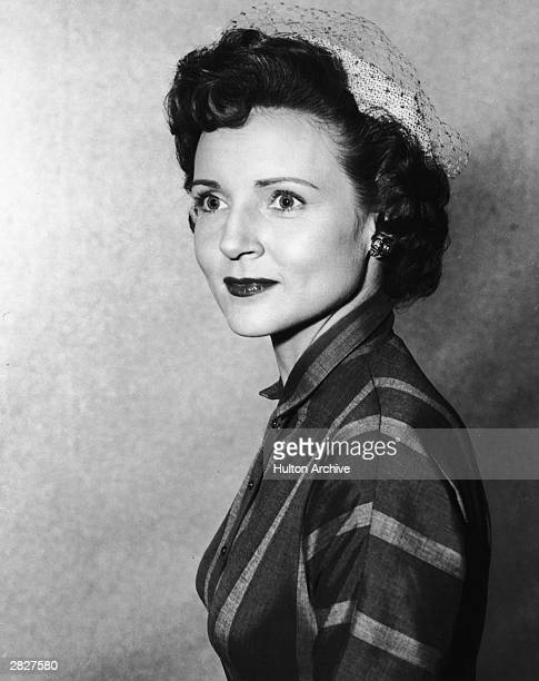 A headshot portrait of American actor Betty White wearing a veiled hat circa 1955