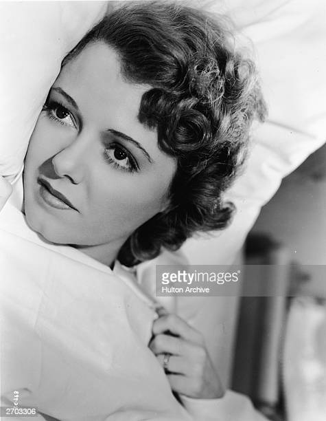 Headshot portrait of American actor Janet Gaynor lying in bed in an unidentified film still circa 1930
